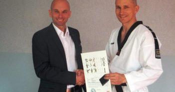 Piotr Maślanka podczas wręczania mu przez przedstawiciela Polskiego Związku Taekwondo Olimpijskiego certyfikatu uzyskania stopnia mistrzowskiego 1dan TKD WTF.